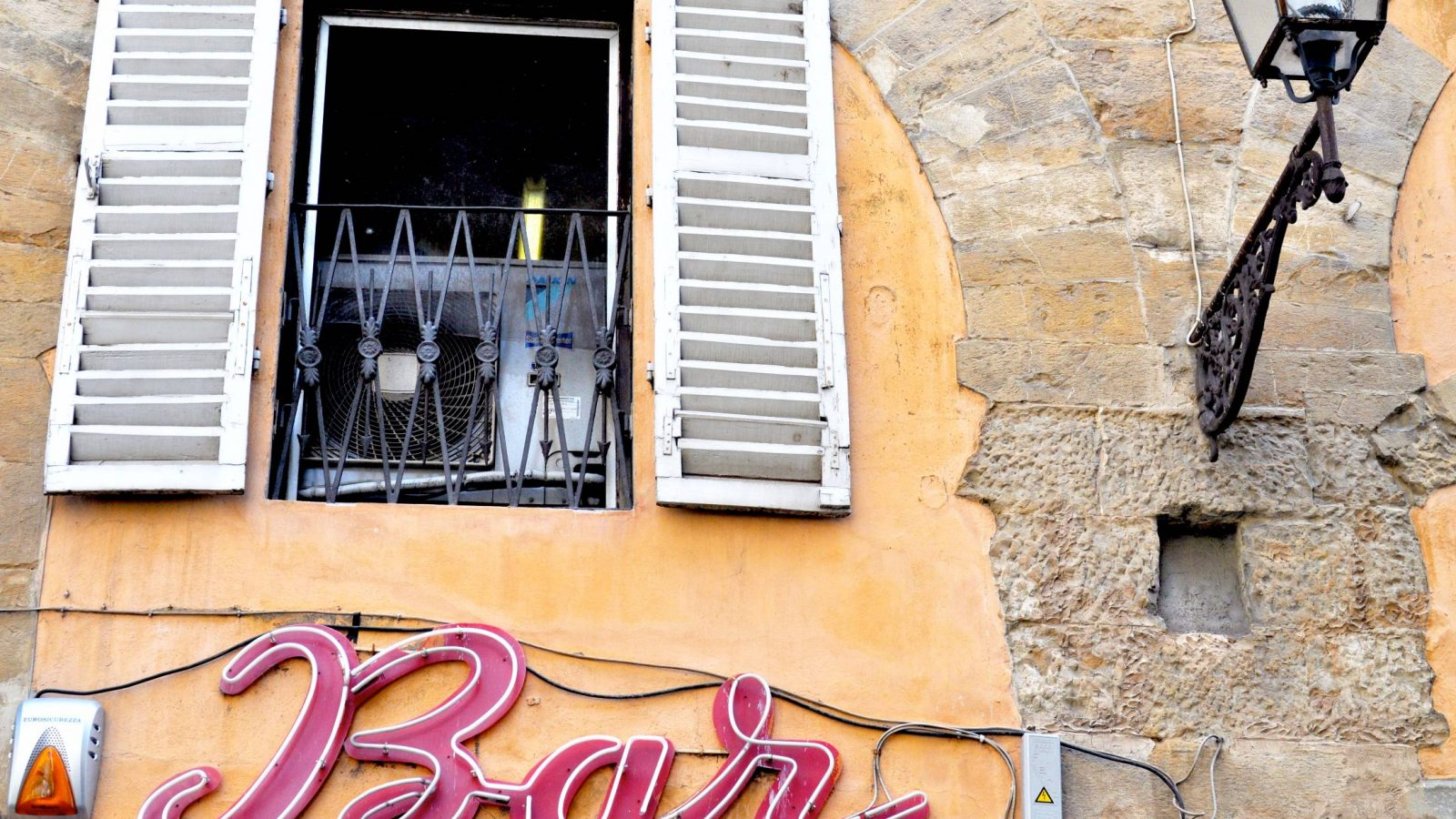 House with a balcony over a bar sign in Florence